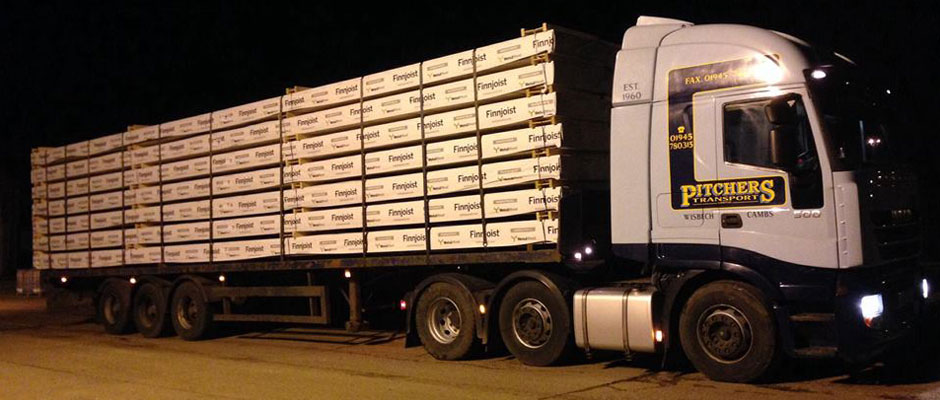 A lorry at night, loaded with pallets